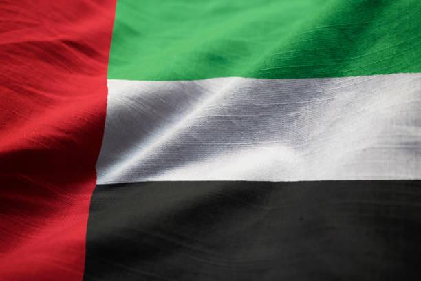 closeup of ruffled united arab emirates flag - uae flag стоковые фото и изображения