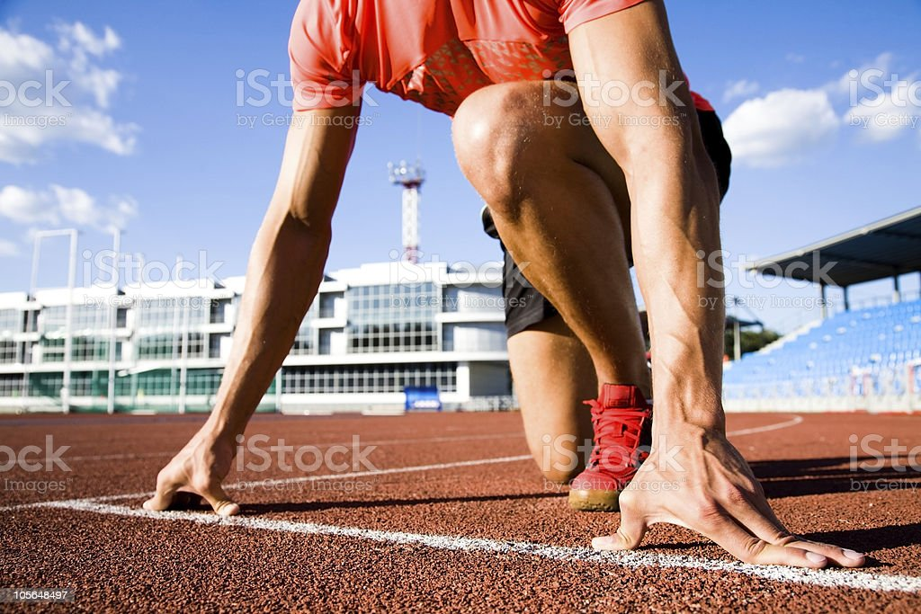 Close-up of runner ready to run on starting line royalty-free stock photo