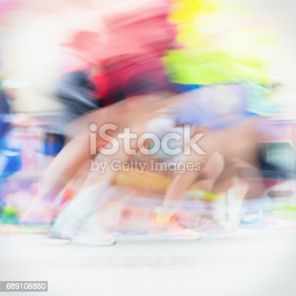 istock Close-up of runners colorful running feet and legs of runners during marathon on city streets. Abstract blurred sport background, place for your text 689106880