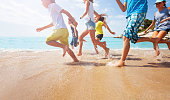 istock Close-up of running kids legs in shallow sea water 859254392