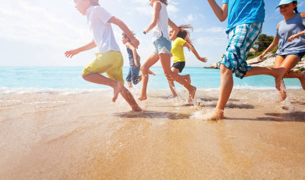 Close-up of running kids legs in shallow sea water - foto stock