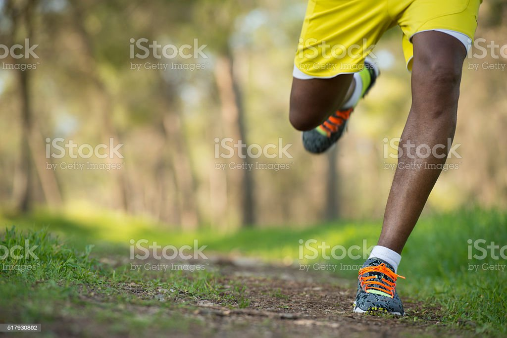 Close-up of running shoes of male legs jogging outdoors. stock photo