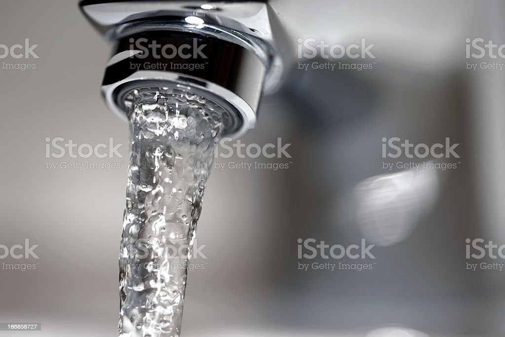 Close-up of running water from a silver faucet stock photo