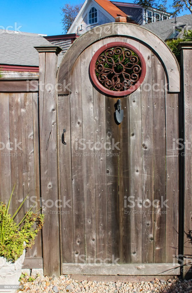 Closeup Of Rustic Wooden Gate With Decorative Round Wrought Iron