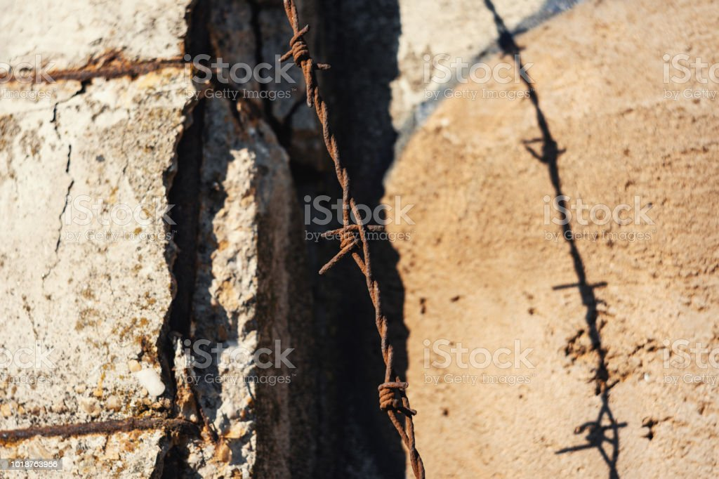 Closeup Of Rusty Barbed Wire Hanging From Dilapidated Cement Wall At