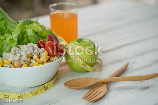 Close-up of salad and measuring tape with green apple on white wooden table.Diet, healthy eating, food and weight loss concept.