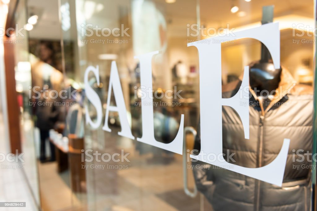 Closeup of Sale sign on clothes, clothing, apparel retail store, shop window in shopping mall stock photo