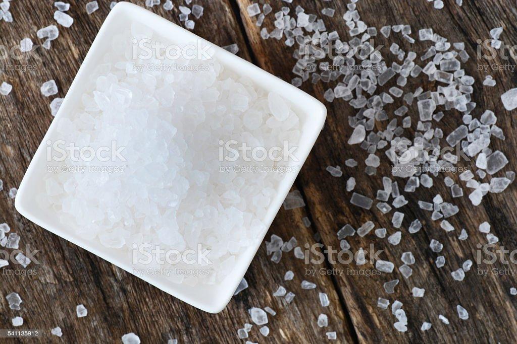 Closeup of salt on wooden table stock photo