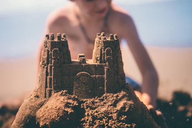 gros plan de sandcastle construit par boy sur vacances d'été - chateau de sable photos et images de collection