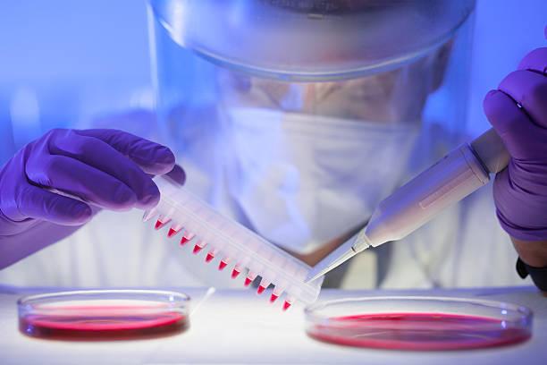 nahaufnahme der wissenschaftler in schützende kleidung - onkologie stock-fotos und bilder