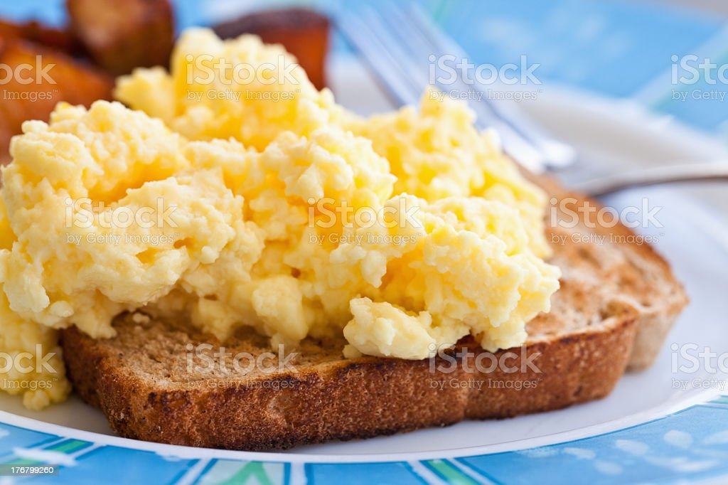 Close-up of scrambled eggs on toast in a white plate stock photo