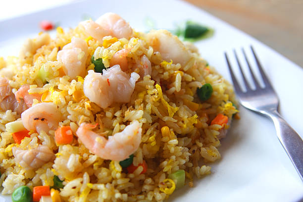 Close-up of seafood fried rice dish served on white plate Delicious prawn and squid fried rice. More Asian Food... fried rice stock pictures, royalty-free photos & images