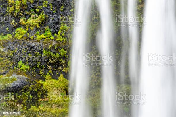 Photo of Closeup of Seljalandsfoss waterfall, Iceland with water falling off cliff in green mossy summer long exposure abstract smooth flow
