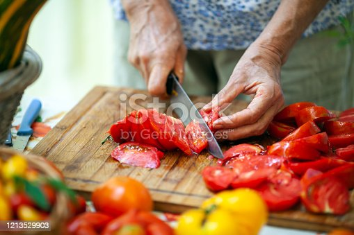Close-up of Senior Adult Woman Slicing Tomatoes on Cutting Board.