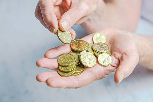 Close-up of senior female hands counting dollar coins stock photo