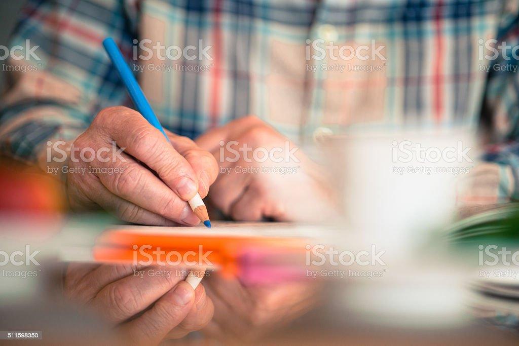 Close-up of Senior Man Coloring Book at Home,  Europe stock photo