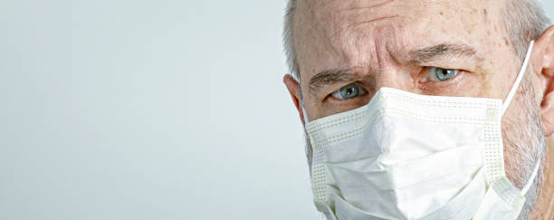Close-Up of Senior Man Wearing Medical Surgical Face Mask stock photo