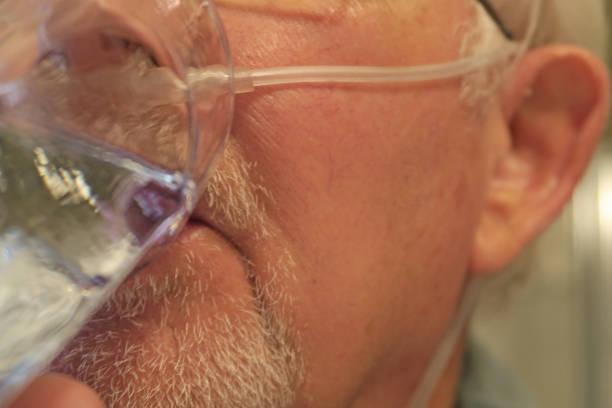 nahaufnahme eines älteren mannes gesicht mit sauerstoff kanüle - senior bilder wasser stock-fotos und bilder