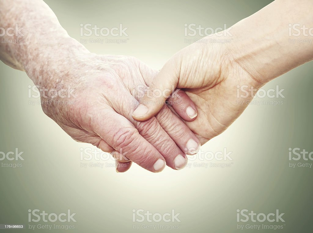 Close-up of senior woman and young woman holding hands royalty-free stock photo
