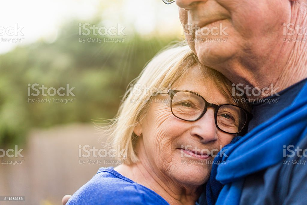 Close-up of senior woman embracing man stock photo
