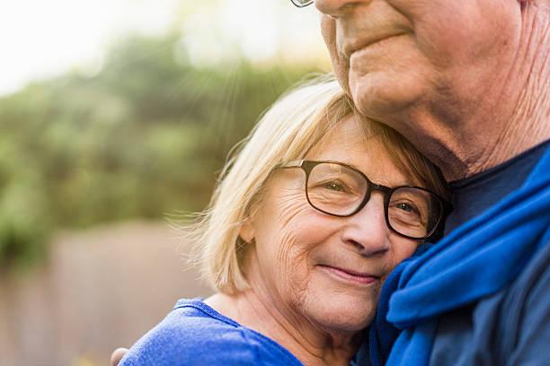 Close-up of senior woman embracing man stock photo