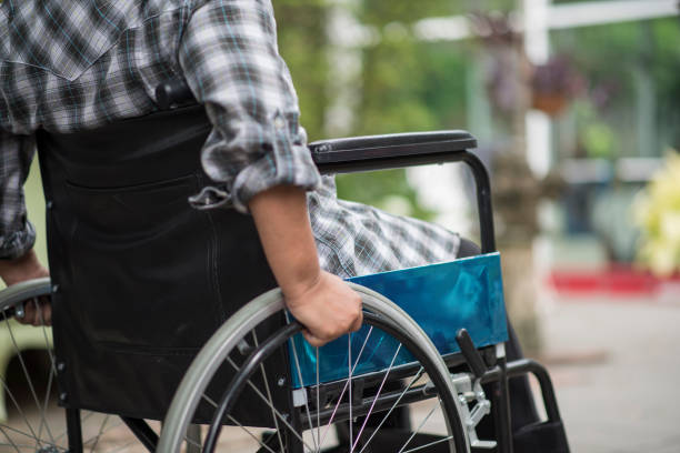 Close-up of senior woman hand on wheel of wheelchair during walk in hospital stock photo