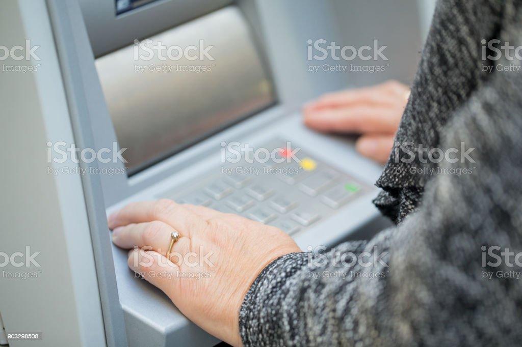 Close-up of senior woman typing pin stock photo