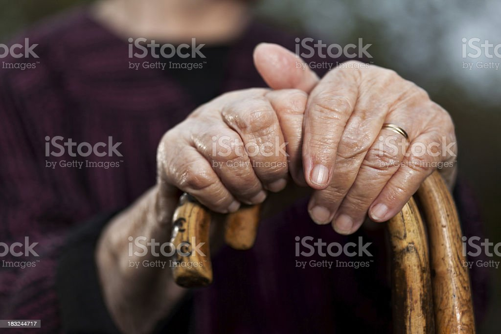 Close-up of senior woman's hands holding her walking sticks stock photo
