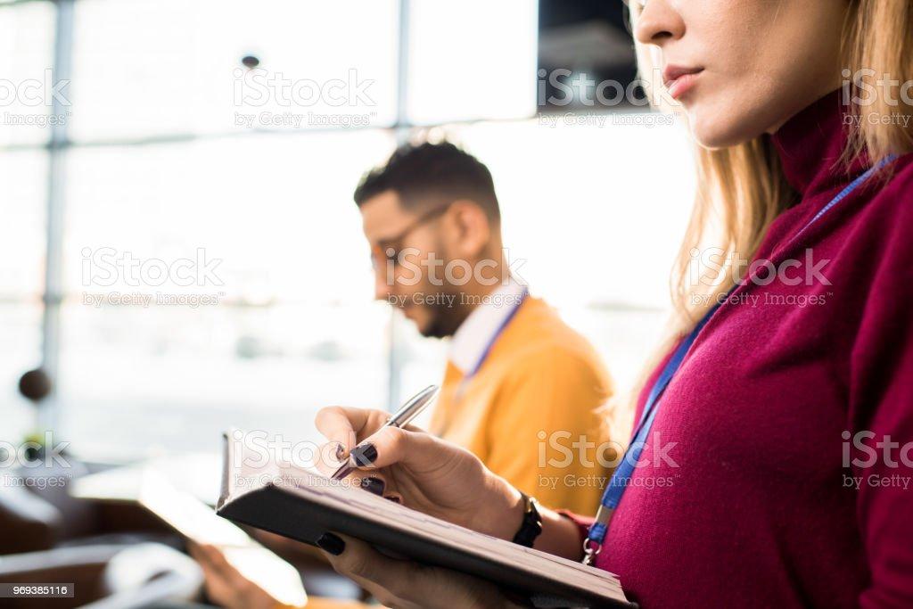 Nahaufnahme von schweren konzentriert junge Frau im Rollkragenpullover tragen Abzeichen Notizen im Tagebuch während der Wiedergabe an Konferenz – Foto