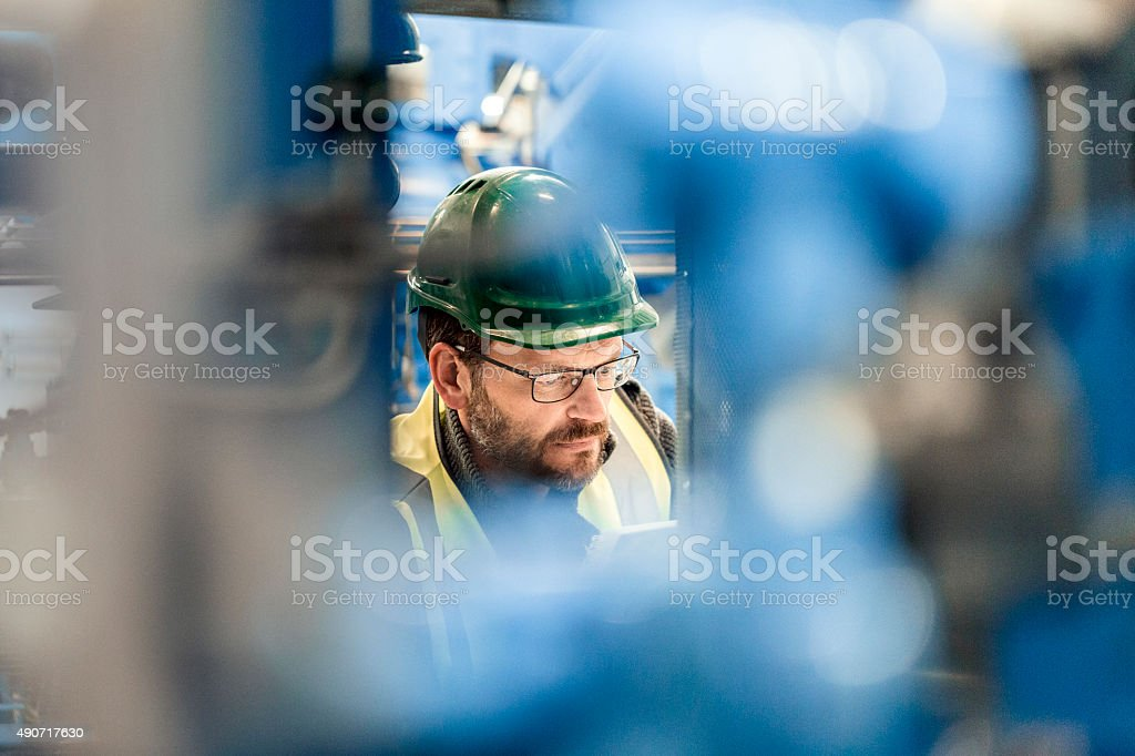 Close-up of serious manual worker at factory stock photo
