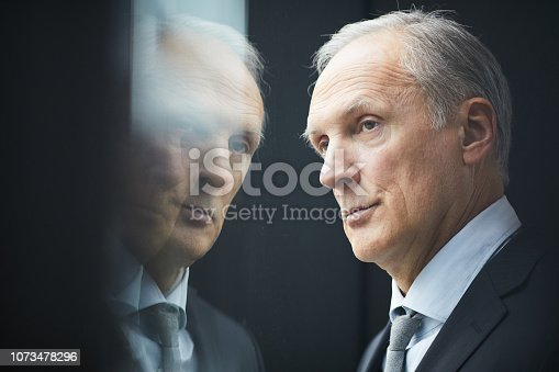 Pensive mature politician looking out window