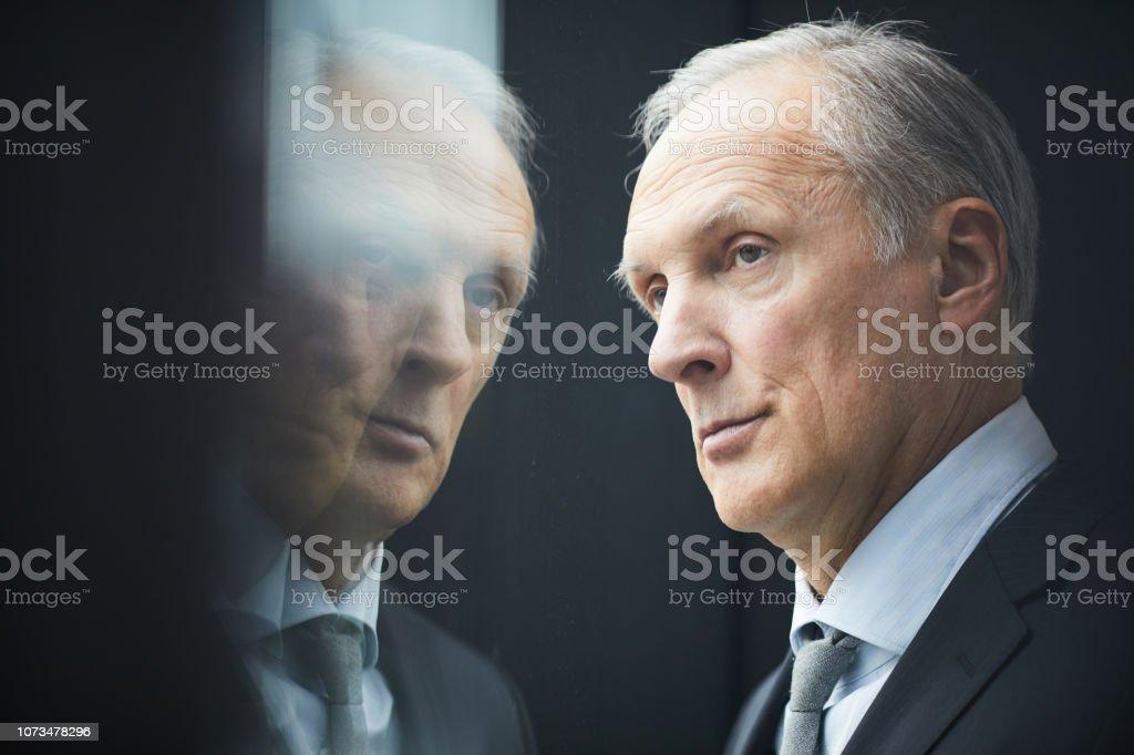 Nahaufnahme von seriöser nachdenklich grauhaarige Reife Politiker mit faltige Stirn schaut aus Fenster, Spiegelungseffekt – Foto