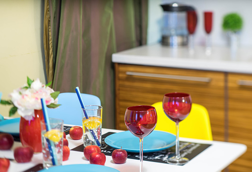 Close-up of served table. Red wine glasses. Water in glass. Wine bottle. Apples.