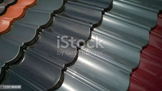 Close-up of several rows of plastic roofing of various colors in shape of tiles,taken diagonally,covered with street dust,as roof will look in reality.Cheap plastic substitution of roof tiles