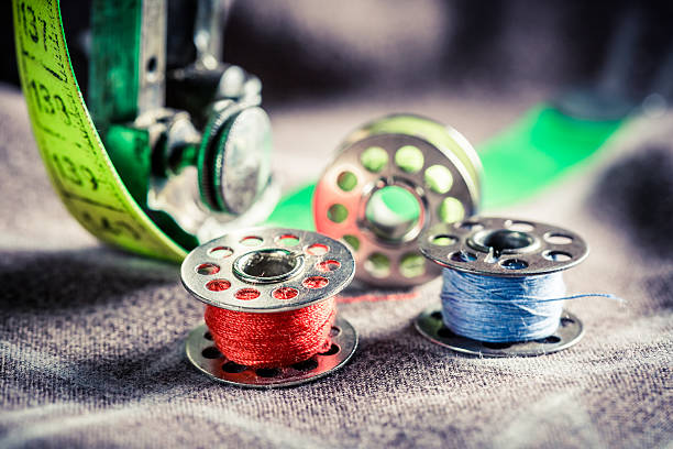 closeup of sewing machine with colored threads and tailor tape - sewing machine needle stock photos and pictures