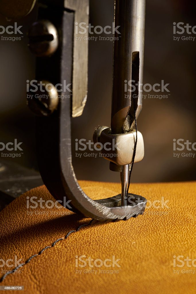 Closeup of sewing machine working part with leather stock photo