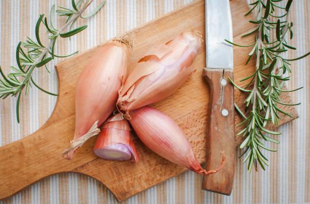 close-up van sjalotjes met verse rozemarijn op snijplank, bovenaanzicht - sjalot stockfoto's en -beelden