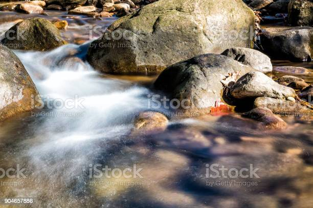 Photo of Closeup of shallow rock stream with smooth running water and waterfall in autumn, stones and long exposure flowing creek