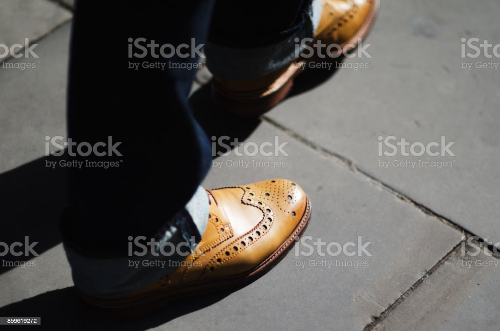 Close-Up of Shoes and Jeans on Sidewalk stock photo