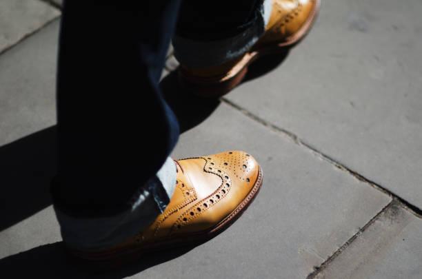nahaufnahme von schuhen und jeans auf bürgersteig - budapester schuhe stock-fotos und bilder