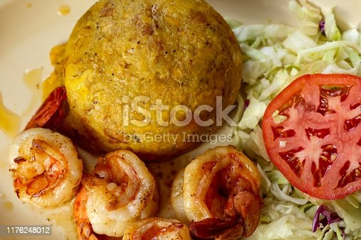 Closeup of Shrimp Mofongo on white plate with lettuce and tomato salad, a traditional Puerto Rican dish