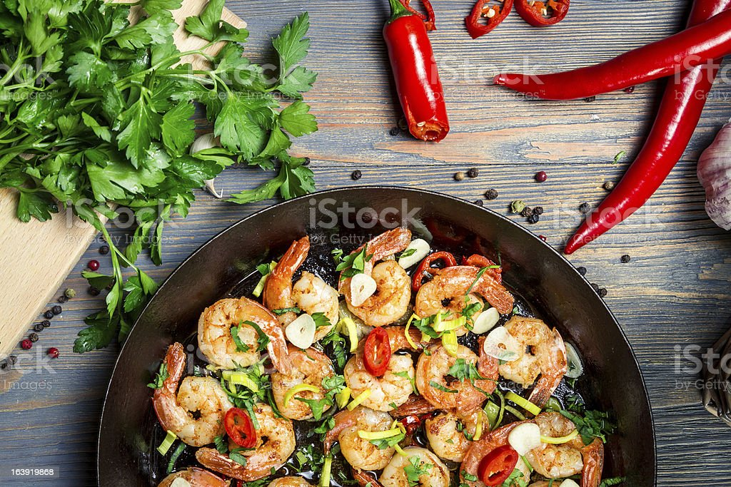 Closeup of shrimps fried on pan and fresh herbs stock photo