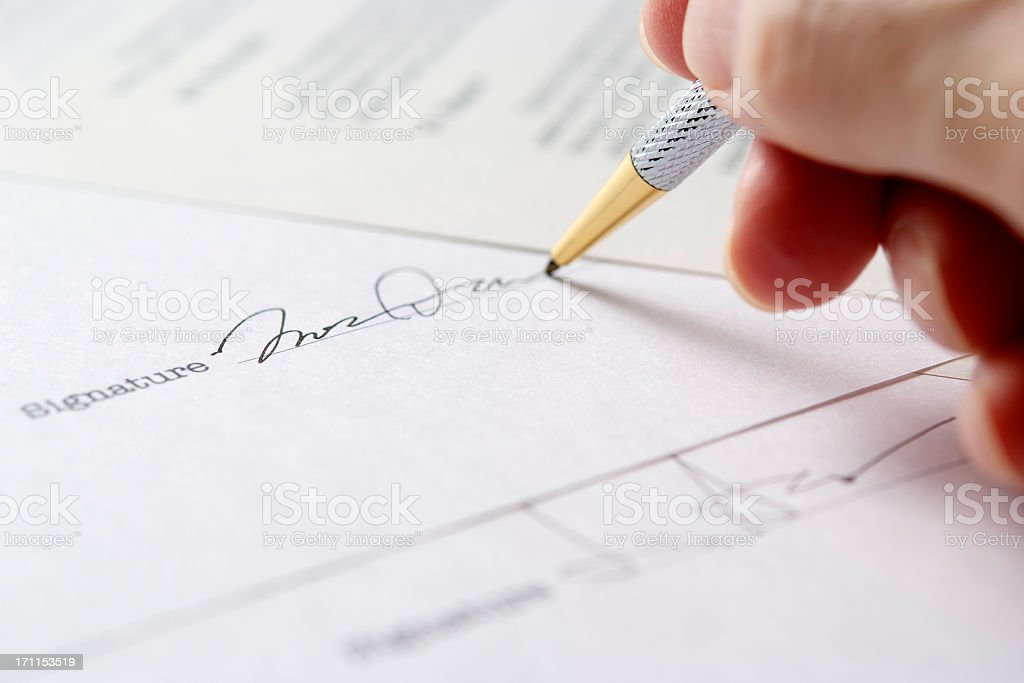 Close-up of signing a contract with shallow depth of field stock photo