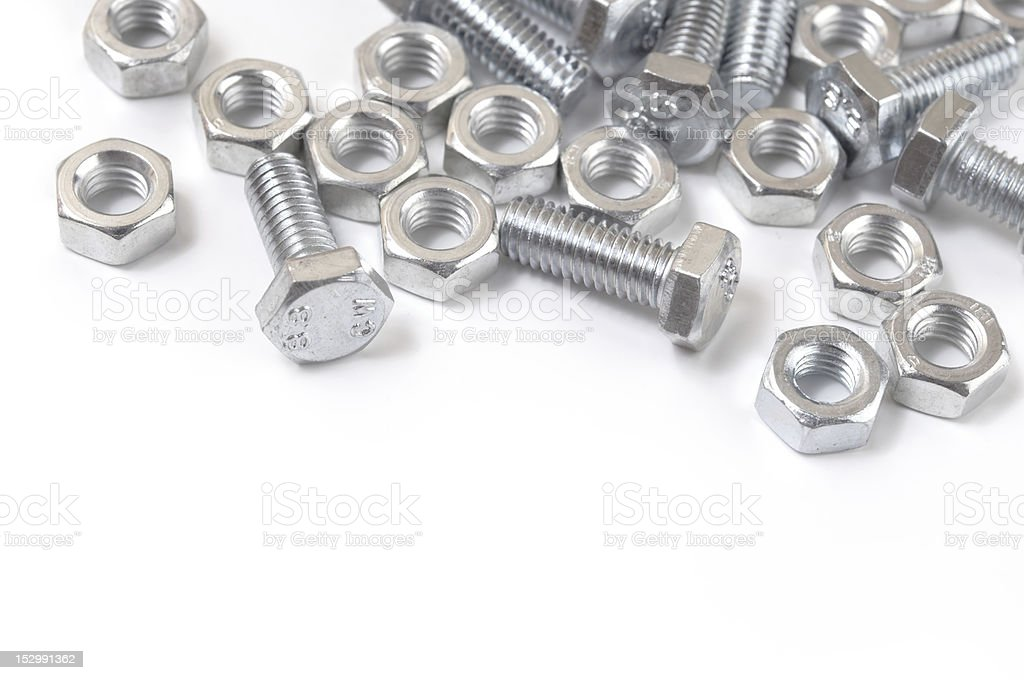 Close-up of silver nuts and bolts on a white surface stock photo