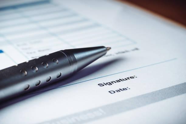 nahaufnahme von silberstift unterzeichnen die vertragspolitik vereinbarung papiere. rechtliche vertragsunterzeichnung. - kündigung arbeitsvertrag stock-fotos und bilder