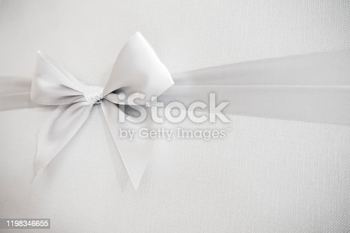Close-up of silver Tied Bow Ribbon on white textured background.