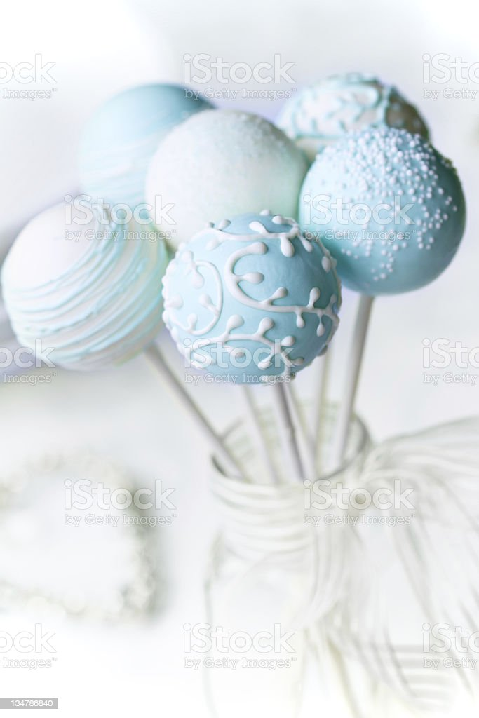 Close-up of six light blue cake pops in a glass container royalty-free stock photo