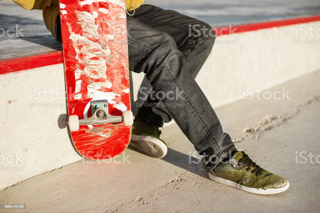 Close-up of skateboarders foot while skating in skate park stock photo