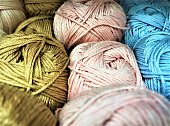Close-up of skeins of cotton yarn with linen blue,pink and khaki colors for knitting and needlework. Selective focus