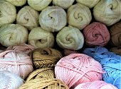 Close-up of skeins of cotton yarn with linen of blue, beige, pink and white colors for knitting and needlework lie for sale on a blurred background of large skeins of white thread. Selective focus